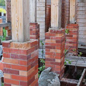 На бетонных опорах – нижняя часть кирпичной стойки, затем брусовая обвязка, потом опять кирпич…