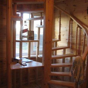 Винтовая лестница на 2-й этаж с полочками и столом.